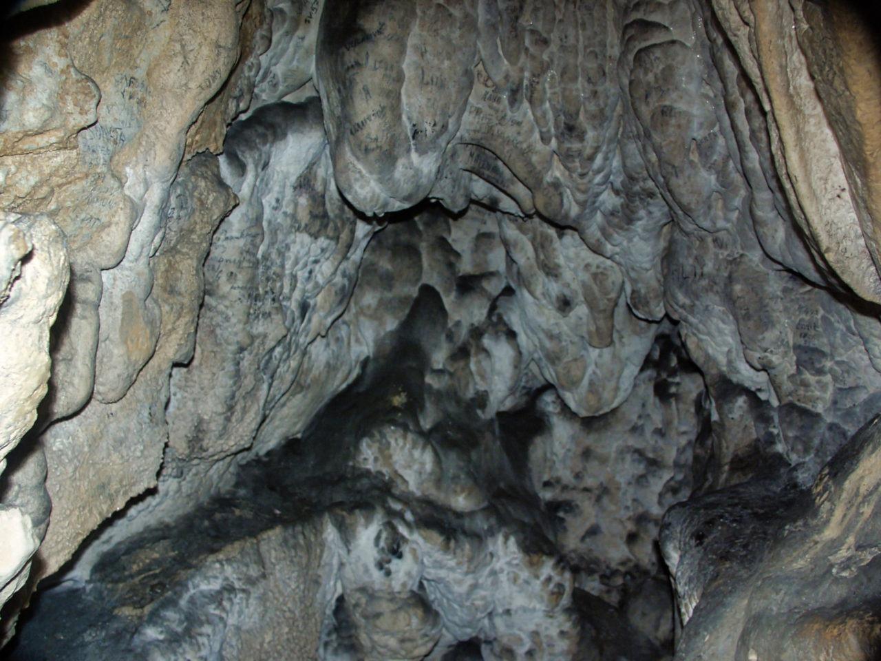 Een grot die pikdonker is. Het enige licht wat je ziet is van de flitser